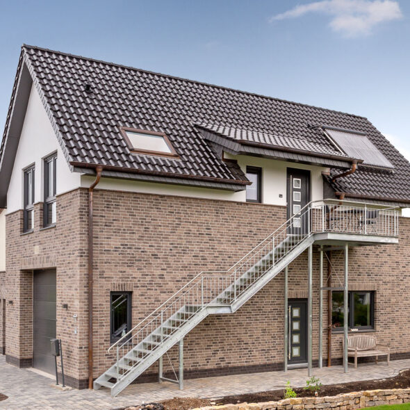 House with flat roof tile J13v in matte volcanic black